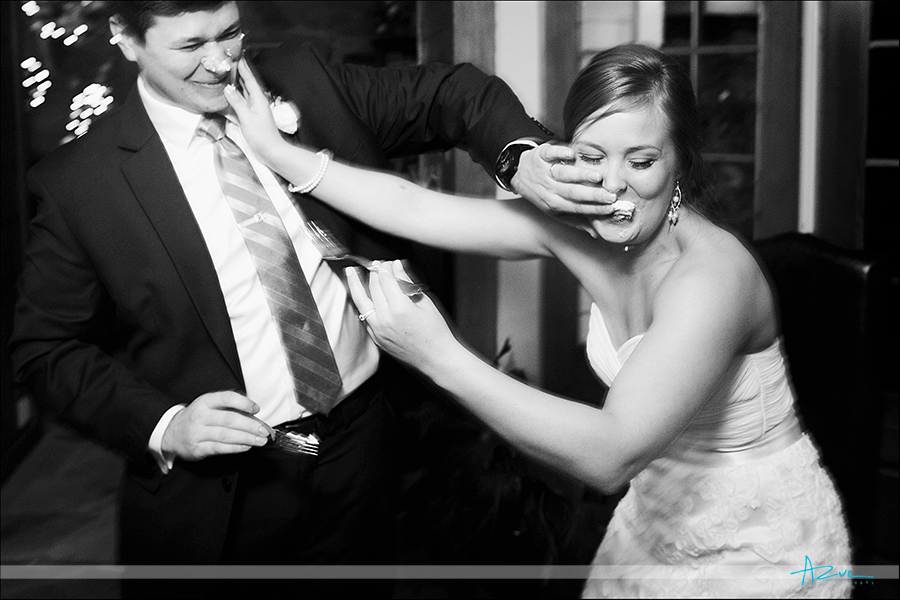 Wedding day tradition action photograph of the couple cake smashing at The Sutherland NC