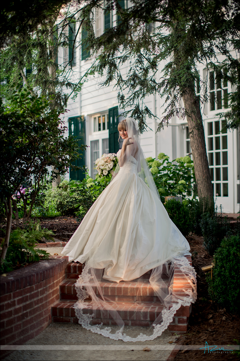 Elegant portrait of bride and veil in courtyard NC