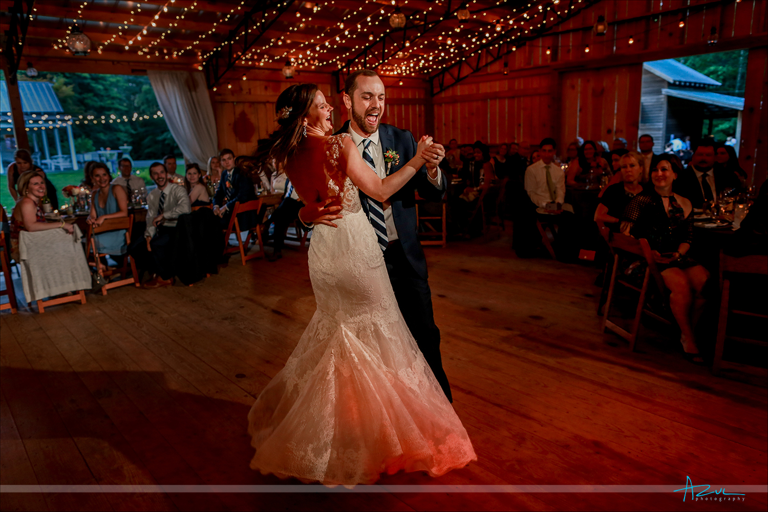 Happy photograph of the wedding bride and groom and their first dance in the barn in Chapel Hill
