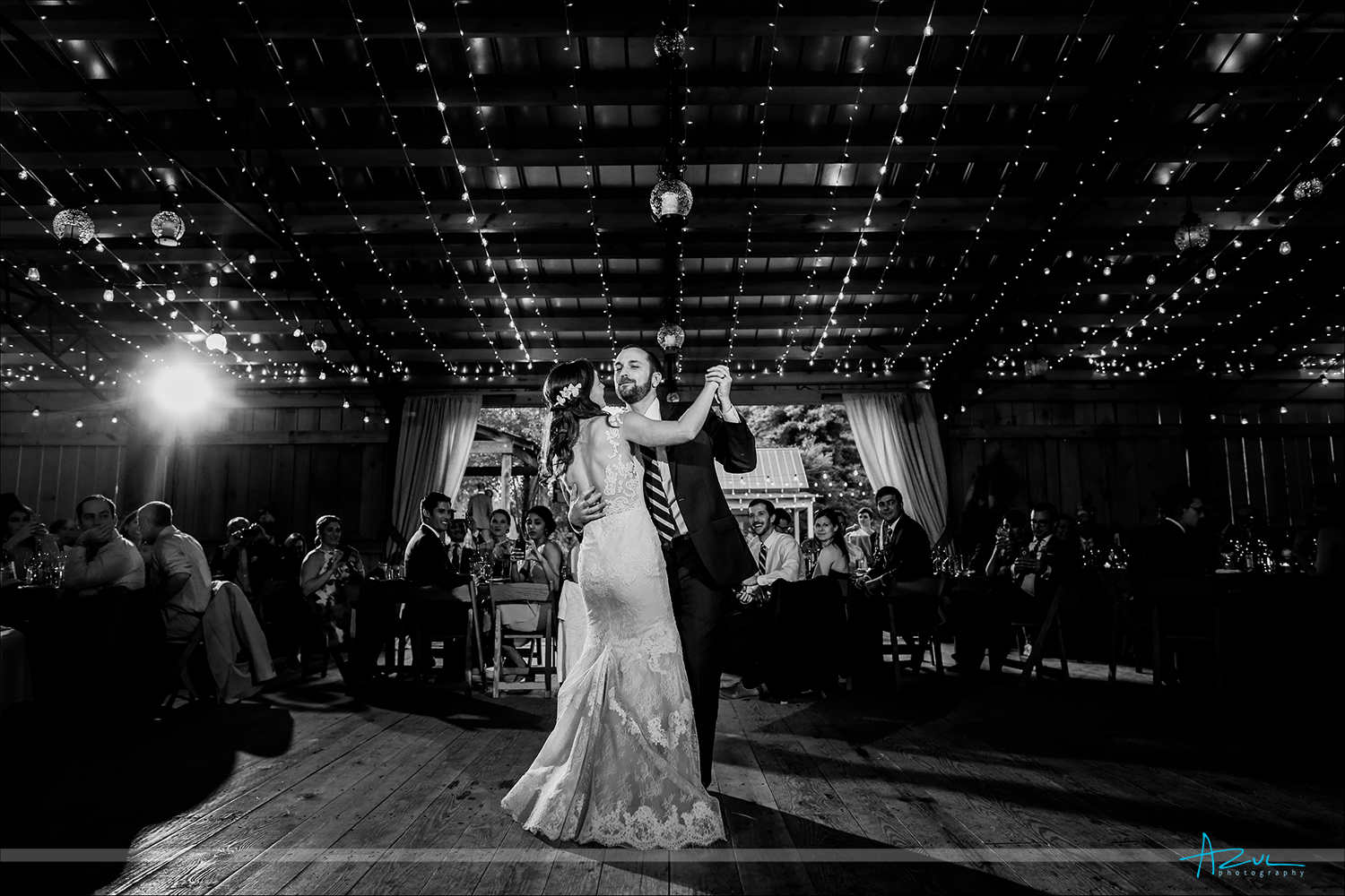 Photography of the groom taking the lead of the bride in their first dance under the twinkle lights in Chapel Hill, North Carolina