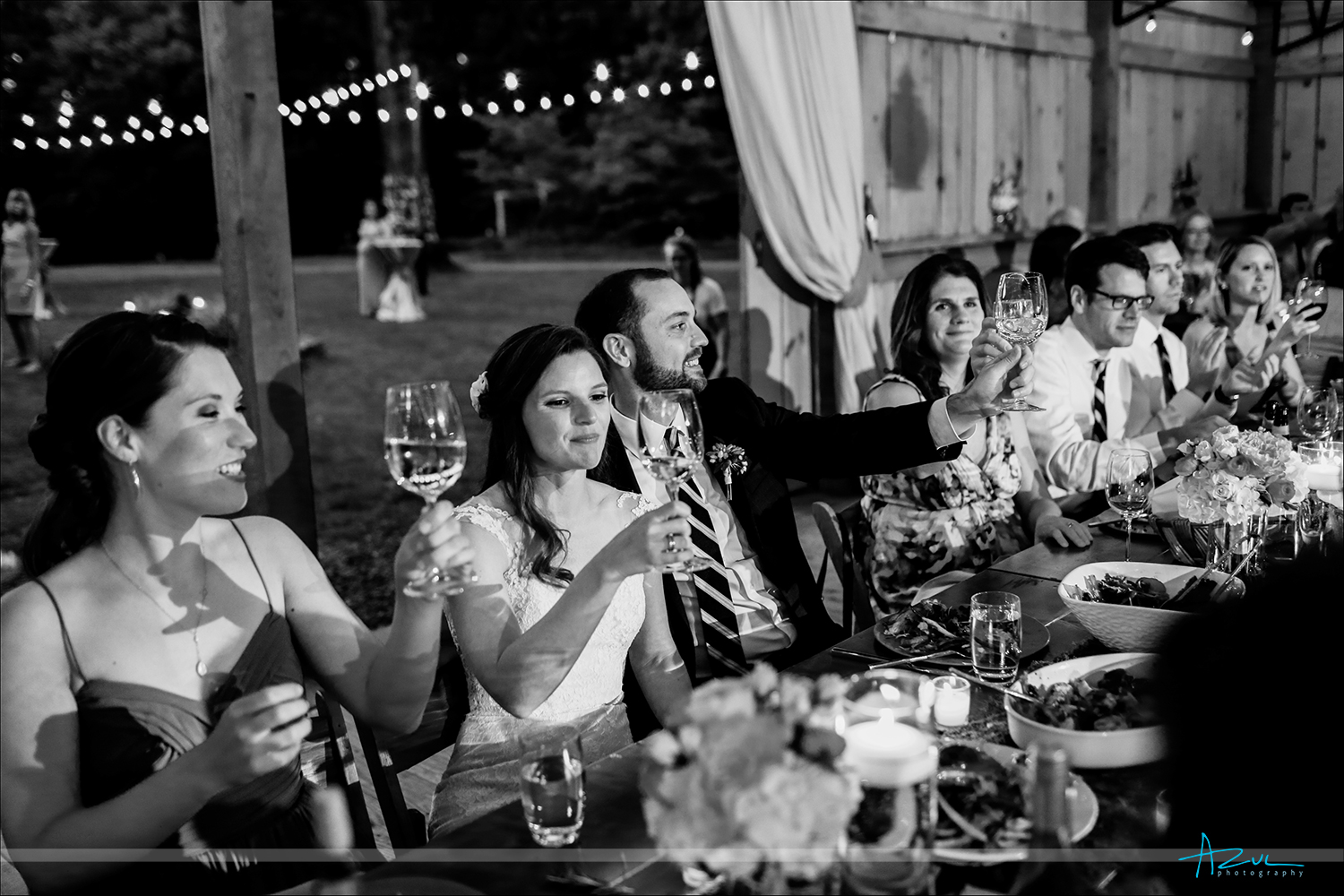 The wedding party toasts with one another at the wedding reception in a barn in Chapel Hill