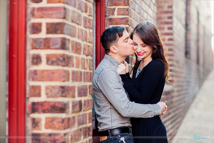 In the ally the couple shares a kiss during their engagement portrait session in downtown Raleigh, North Carolina