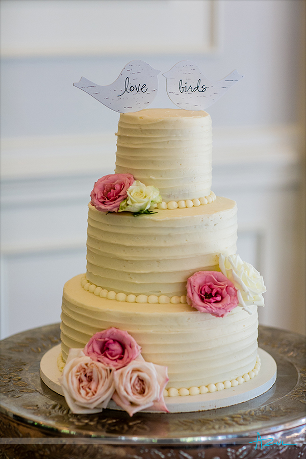 Delicious cake from Sweet Memories is topped with love birds while at the reception at Highgrove Estate in Fuquay Varina, NC.