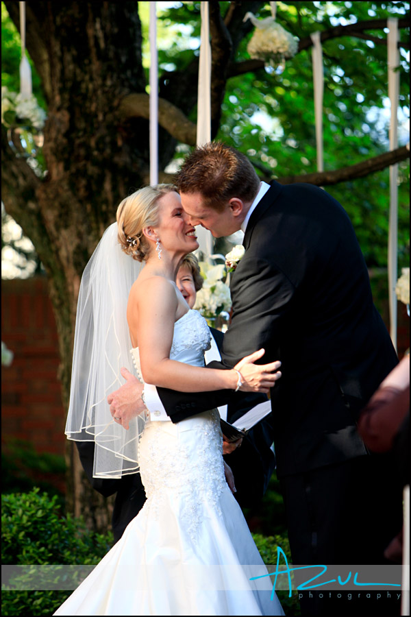 The groom kisses his bride during the wedding ceremony at the Carolina Inn..