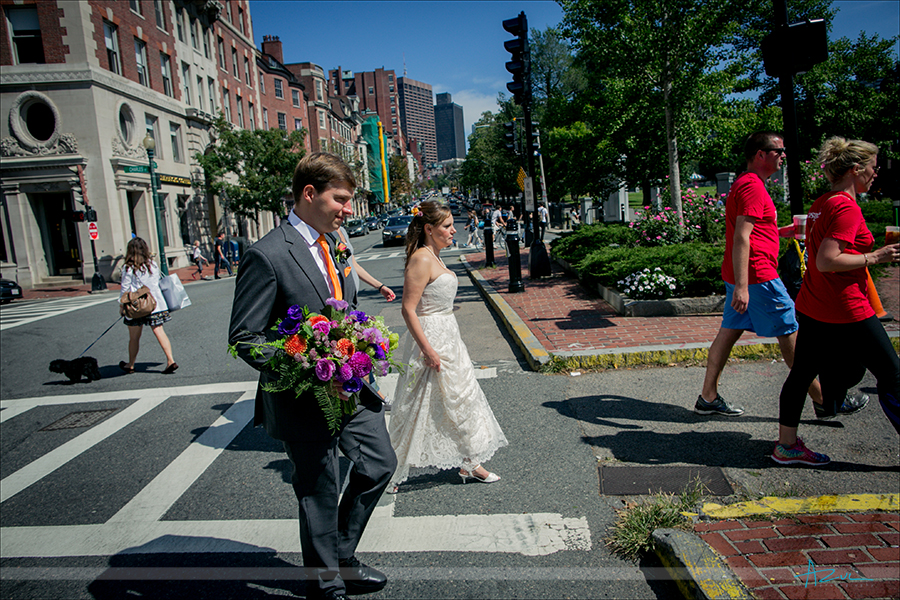The bride and groom walk to the next portrait location while in Boston Mass