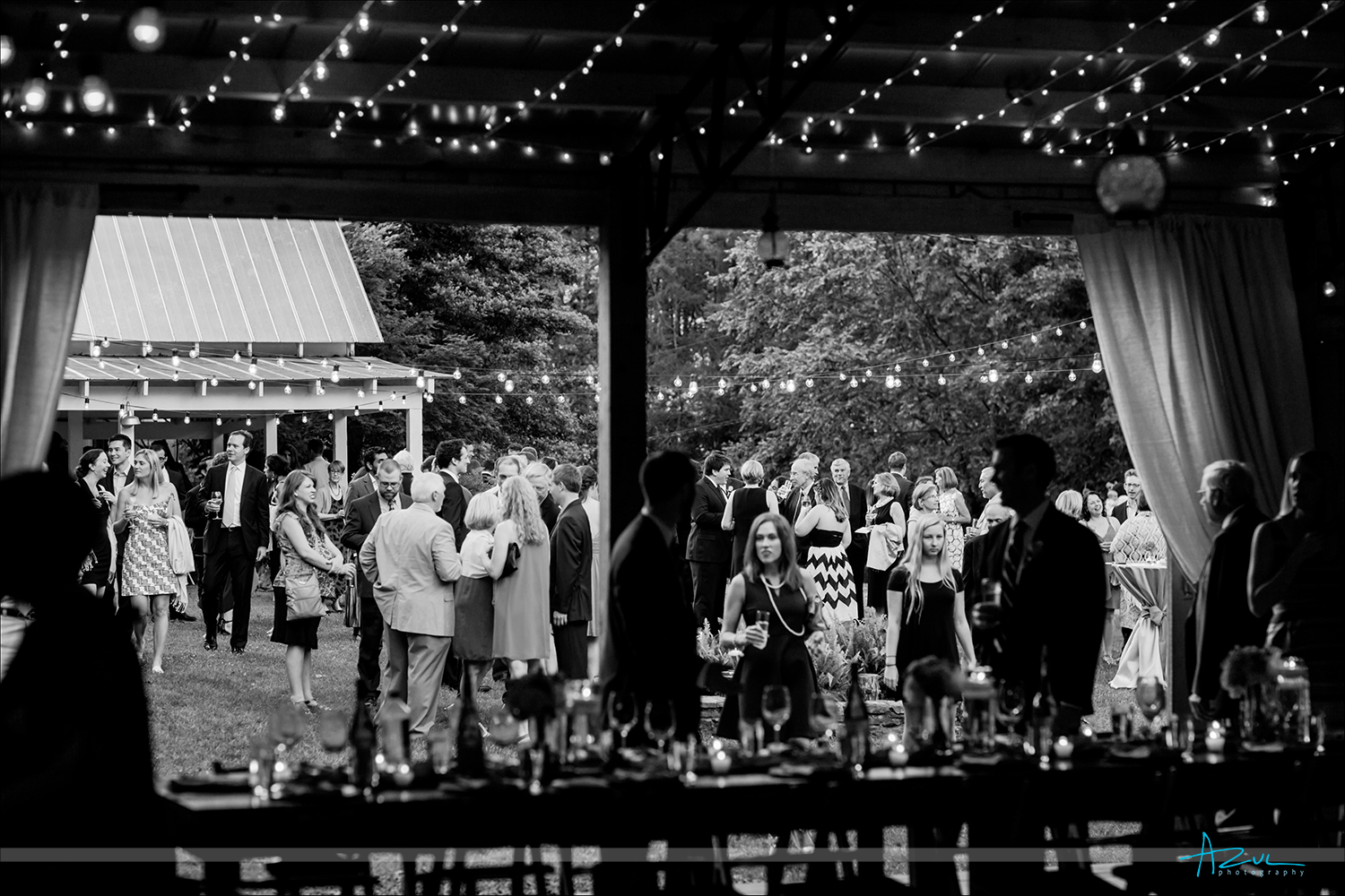 Barn wedding reception photograph of preparation with cocktail hour in the back ground in North Carolina