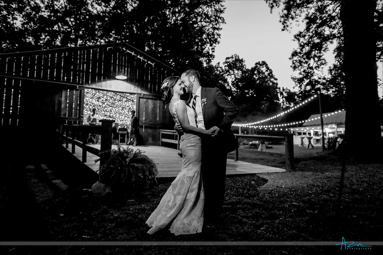 The happy bride and groom have a wedding day portrait created by the photographer just outside the barn during the reception in North Carolina.