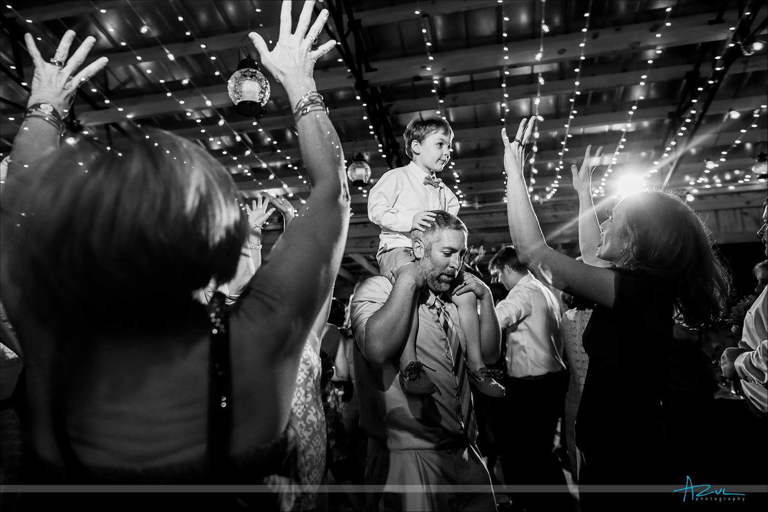 Photographer captures moment of a father and son dancing together inside a barn during a wedding reception in North Carolina