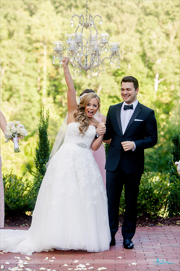 The bride celebrates with a fist in the air after getting married at Highgrove Estate in Fuguay Varina, North Carolina.