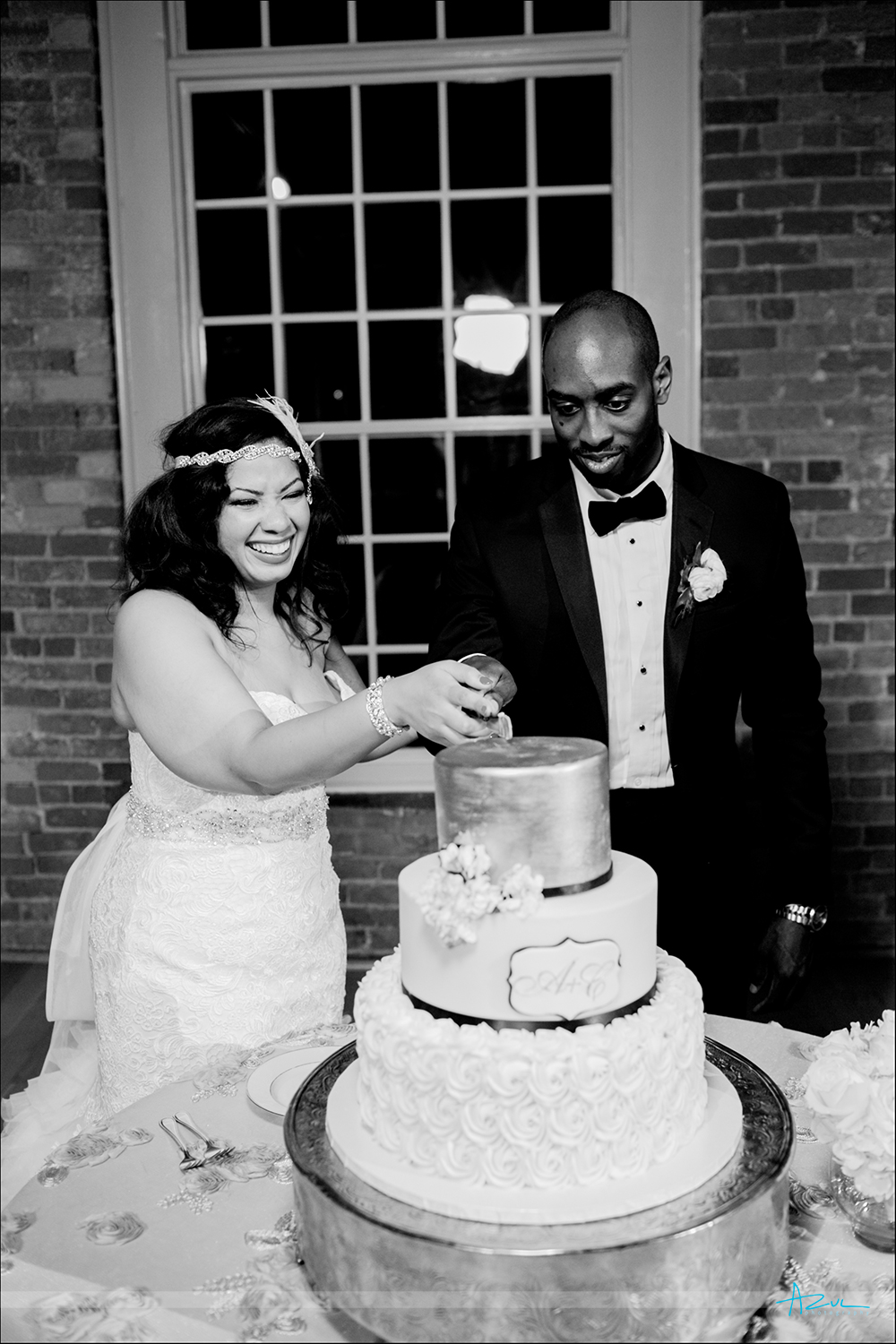 Cutting th cake can be a fun and it was at this wedding at The Cotton Room in Durham located just outside of Raleigh