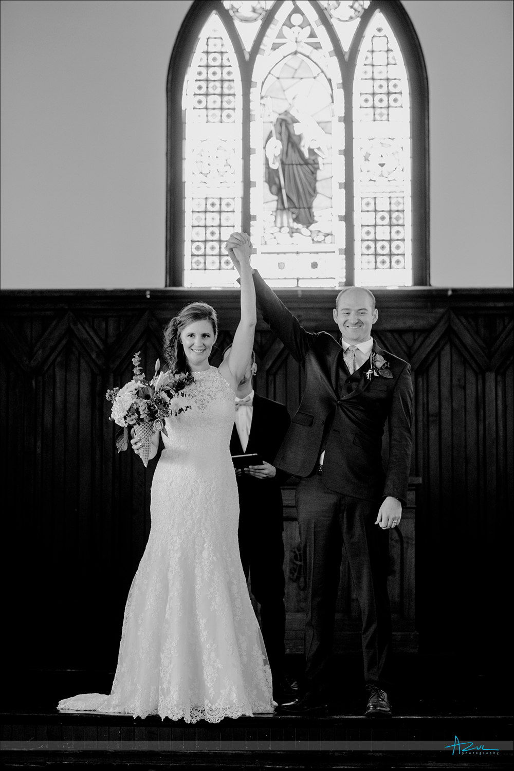 The bride and groom raise their arms in victory after the wedding as the photographer captured this perfectly in Raleigh NC